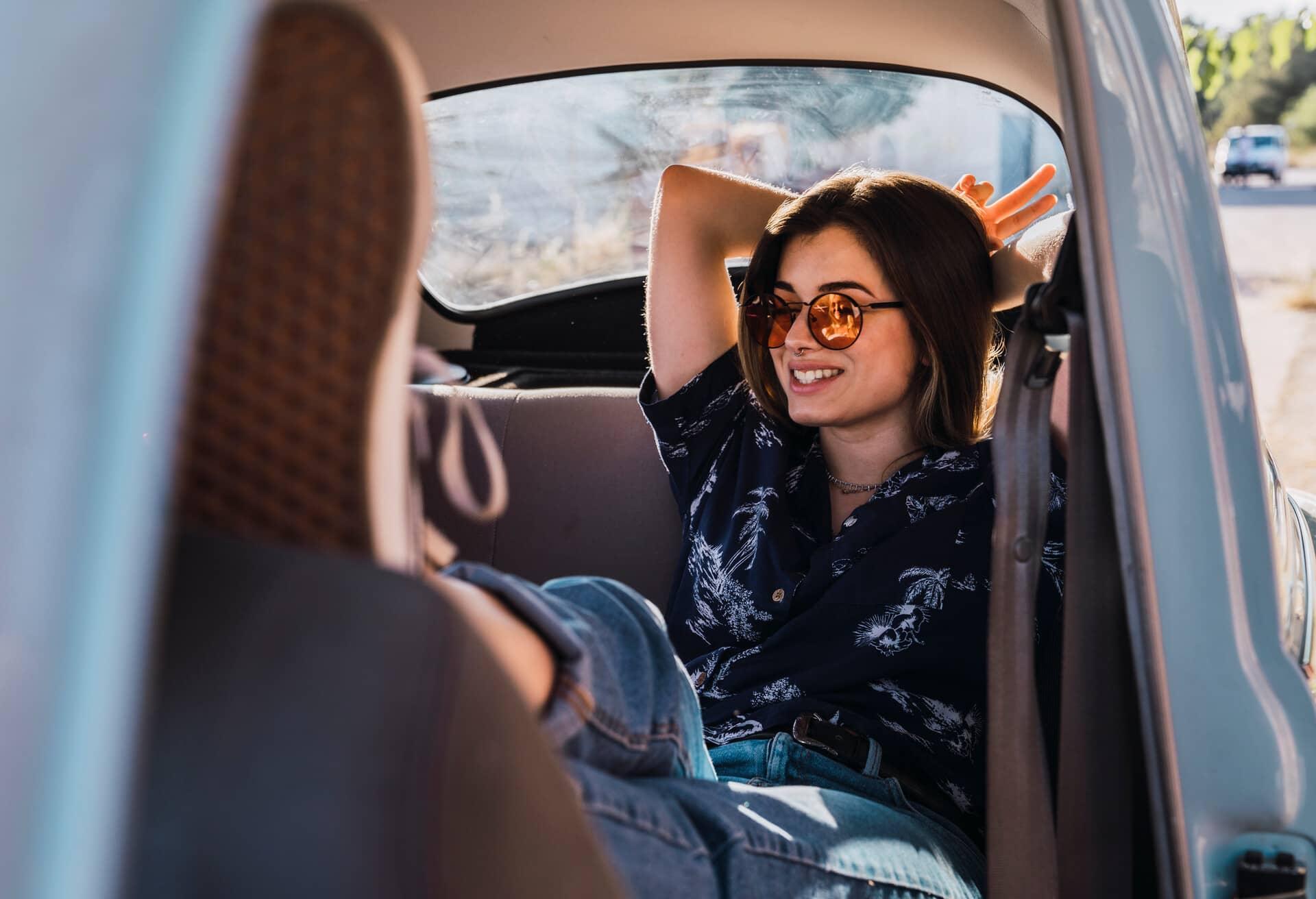 Дівчинка на задньому сидінні насолоджується автомобільною поїздкою.